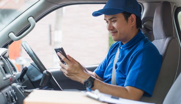 Male employee looking at phone in work van.